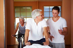 caregiver with old man having physical exercise